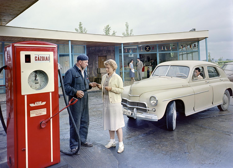1959. július 23. Fiatal nő átadja a kifizetett üzemanyagról a pénztárblokkot a benzinkutasnak egy balatoni ÁFOR benzinkútnál. Jobbra, egy Warszawa M201-es típusú gépkocsi várakozik a tankolásra.   A felvétel készítésének pontos helye ismeretlen. MTI Fotó: Járai Rudolf