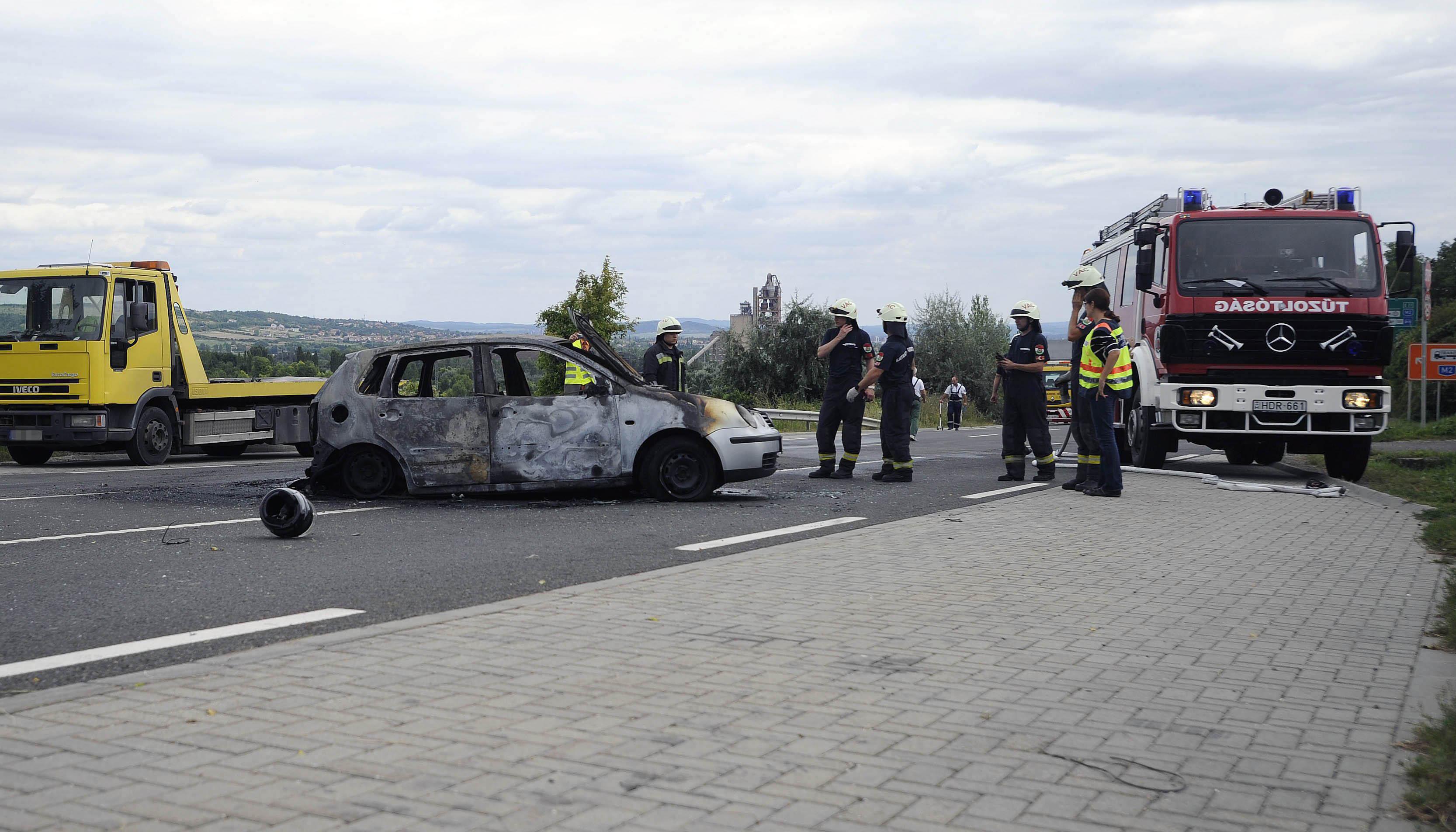 Vác, 2016. augusztus 13. Rendőr és tűzoltók egy kiégett személyautónál a 2-es főúton Vác térségében, ahol a személygépkocsi egy motorossal ütközött össze 2016. augusztus 13-án. A balesetben mindkét jármű kigyulladt, a motorkerékpár vezetője életét vesztette, utasa súlyosan megsérült. Az autóban ülők közül egy férfi súlyosan, két nő könnyebben megsérült. MTI Fotó: Mihádák Zoltán
