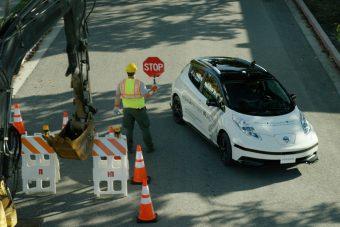 A sofőr segít a robotnak autót vezetni