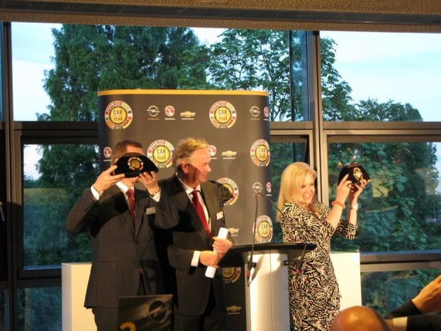 Karl-Friedrich Stracke, az Opel, és Susan Docherty, a Chevrolet első embere emeli magasra a trófeát. Közöttük Az év autója zsűri svéd elnöke, Hakan Matson
