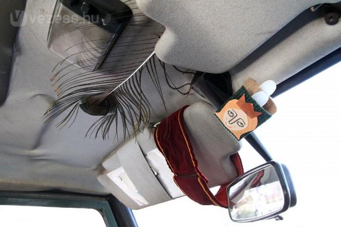 Modern, izléses autóbelső, pávatollal és az Elvarázsolt disznó című meseopera főhősével