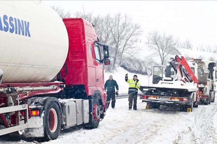 Elakadt teherautót próbálnak menteni Győr határában a 81-es főút egyik autópálya-felhajtójánál. Fotó: MTI