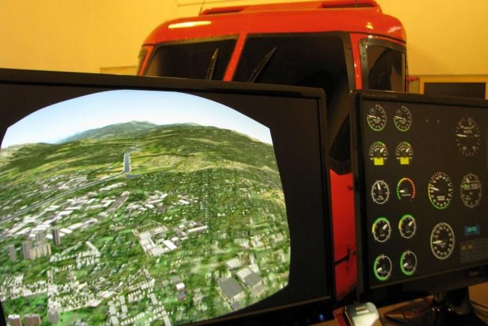 A bal oldali monitoron látható képet vetíti ki gömbtükörre, majd onnan tükrözve a szimulátor belső ablakfelületeire a rendszer: ezért a torzított kép.