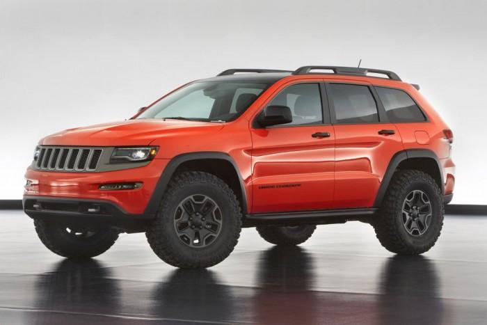 jeep Grand Cherokee Trailhawk Concept - Hathengeres dízelmotorral, de az SRT optikai kiegészítőivel lép színre az extrém Grand Cherokee: mattfekete-vérnarancs fényezés, 35 colos terepabroncsok kivágott kerékjáratokban, egyedi hasvédő lemezek, dupla vonóhorog, Mopar küszöbvédő tereprács.