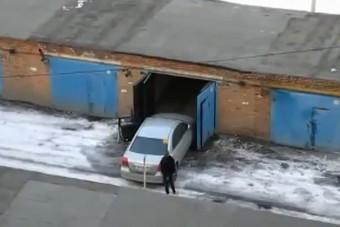 Női sofőr küzdelme a garázsajtóval