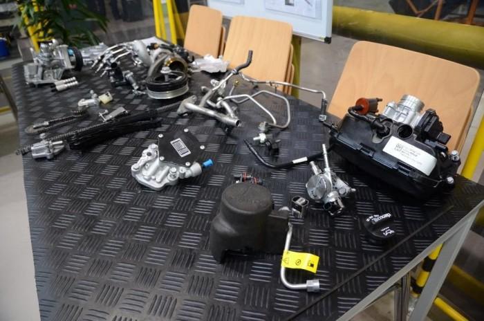 Az 1 literes, 3 hengeres turbómotor elemeire bontva, az egyik asztalon...