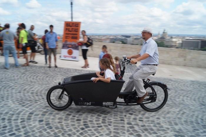 A budapesti bringázás egyik messiása saját, gyerekszállító elektromos teherbringájával jött el a sajttájra. Éppen lányaimat viszi a fekete gépben, akiktől persze azóta se hallok mást, minthogy mikor veszünk ilyet