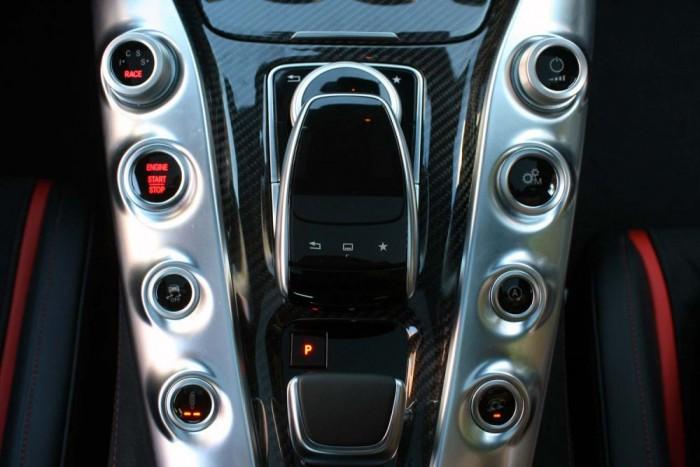 Bal fent állíthatók az üzemmódok egyénitől a kényelmesen, sportosan, még sportosabban át a versenyprogramig. Alatta az indítógomb, a menetstabilizáló és a lengéscsillapító karakterisztikájának kapcsolója. Jobb oldalt a hangerő, a váltóbeállítás, az alapjárati motorleállítás és a kipufogó-hangosítás kapcsolója