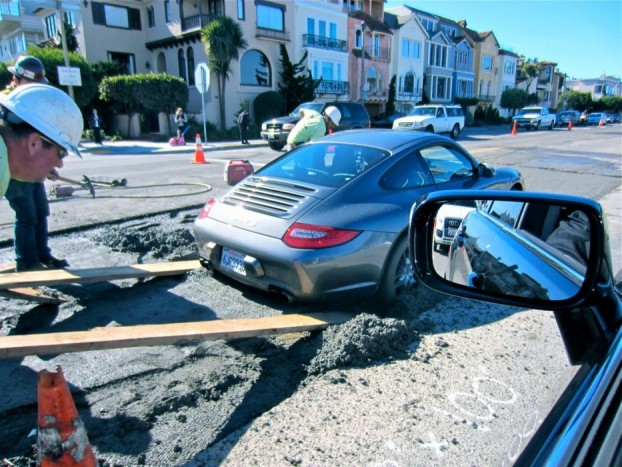 A gazdagok mindig időhiányban szenvednek. A képen szereplő Porsche 911 sofőrje is torlódást akart kerülni, de helyette a friss beton fogja lett. Habár hamar kimentették, kalandja sokba fájhatott, a teljes futóművet és fékeket tisztíttatni kell, de valószínűbb, hogy cserélni kellett.