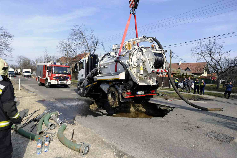 Budapest, 2016. február 27. Tûzoltók egy szennyvíz-szippantó teherautó kiemelésén dolgoznak a XVIII. kerületi Halomi úton 2016. február 27-én, miután a jármû alatt menet közben beszakadt az útburkolat. MTI Fotó: Mihádák Zoltán