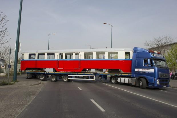 Budapest, 2016. április 6. A hûvösvölgyi gyermekvasút felújított BAW sorozatú személykocsiját szállító speciális jármû kanyarodik ki a MÁV fõvárosi XIV. kerületi Dózsa György úti javítómûhelyébõl 2016. április 6-án. A 66 éves, 10 tonnás, 16 méter hosszú kocsit, amelyet a Ganz Gépgyárban 1950-ben készítettek, daruval emelik a szintén felújított forgózsámolyokra a gyermekvasút hûvösvölgyi végállomásán. MTI Fotó: Lakatos Péter