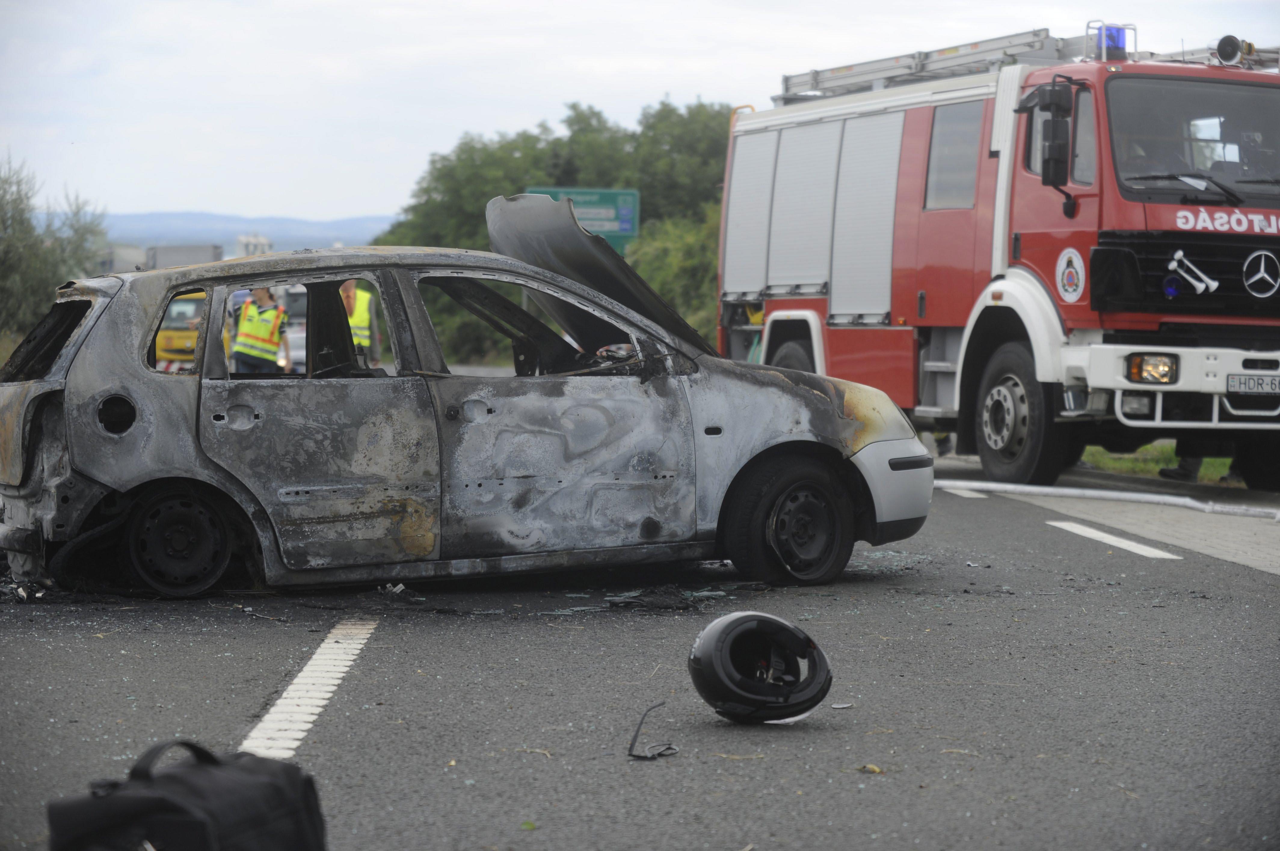 Vác, 2016. augusztus 13. Bukósisak egy kiégett személyautó mellett a 2-es főúton Vác térségében, ahol a személygépkocsi egy motorossal ütközött össze 2016. augusztus 13-án. A balesetben mindkét jármű kigyulladt, a motorkerékpár vezetője életét vesztette, utasa súlyosan megsérült. Az autóban ülők közül egy férfi súlyosan, két nő könnyebben megsérült. MTI Fotó: Mihádák Zoltán