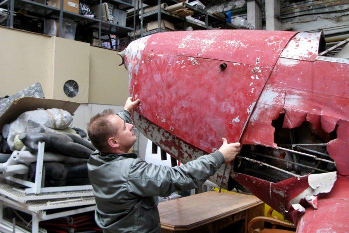 Ungár László emeli le a burkolatot, hogy megmutassa a motort