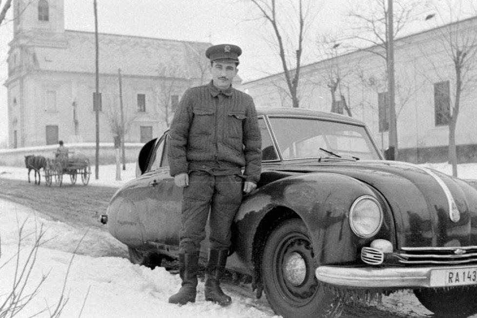 """A legérdekesebb képpel kezdünk, egy különleges, ritka típus mellett áll a sarló-kalapács sötét éveit védő """"rendőr"""", 1954-ben. Ez a Tatra T87 korának legkülönösebb járműve volt, és semmi nem utal arra, hogy bármilyen rendvédelmi szervet szolgálna, kivéve a rendszám. Elvileg csak csak a Rendőrség saját tulajdonú autói kapnak RA és RB rendszámokat."""