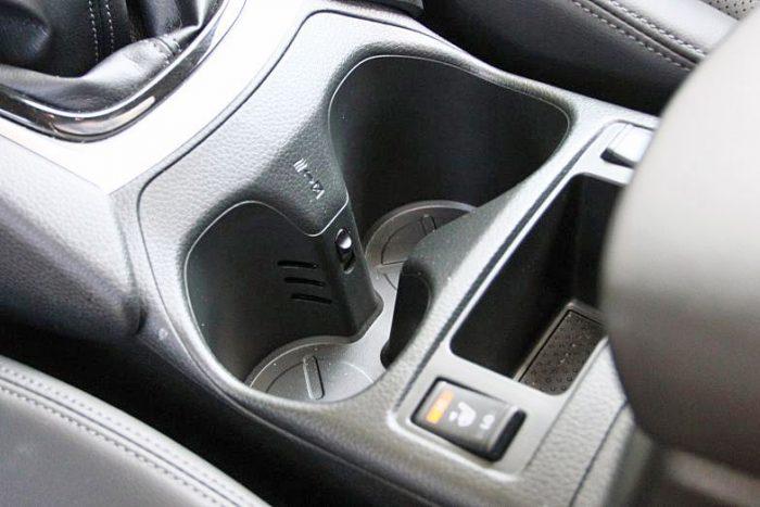 A Nissan egész olcsón megoldotta a hűthető pohártartót. Egy apró kis kapcsolóval szabályozható, hogy a légkondi hűvös levegője a pohártartóba is bejusson-e