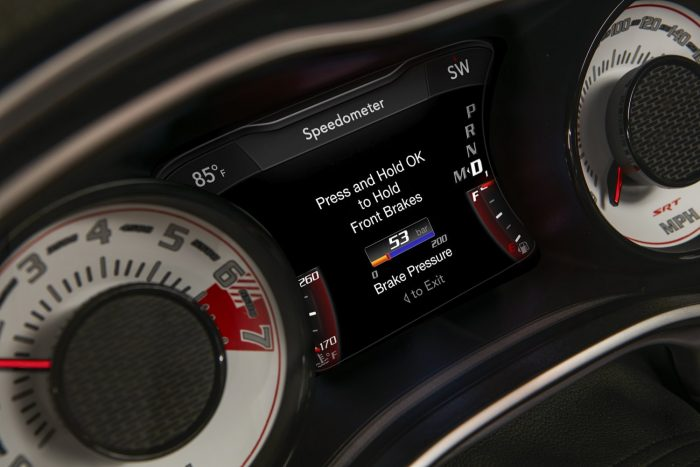 The line lock brake pressure gauge on the 2018 Dodge Challenger SRT Demon's 7-inch instrument cluster screen is centered between the exclusive SRT Demon white face gauges.