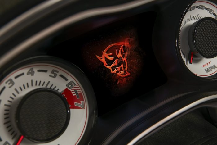 The Demon logo startup screen displayed on the 2018 Dodge Challenger SRT Demon's 7-inch instrument cluster screen centered between the exclusive SRT Demon white face gauges.